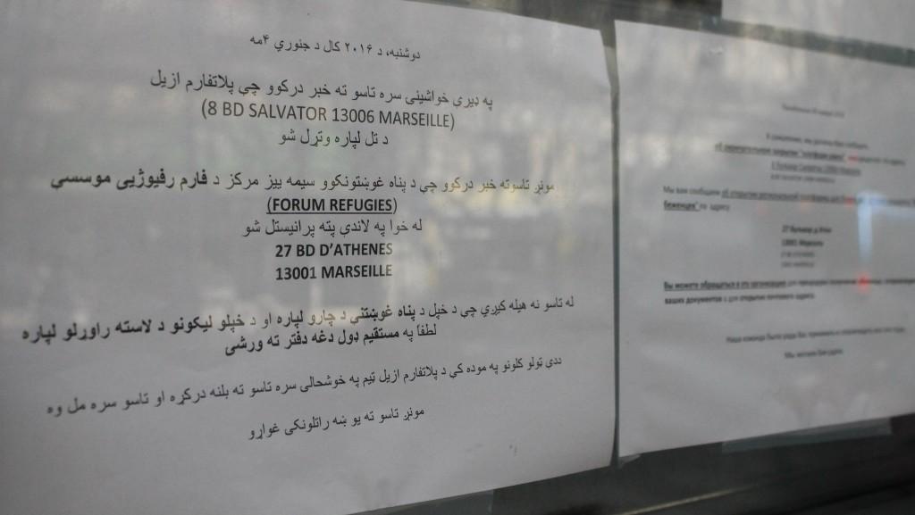Sur la vitrine de l'ancienne plateforme, des affiches expliquent dans plusieurs langues comment se rendre au nouveau lieu, pas encore ouvert.