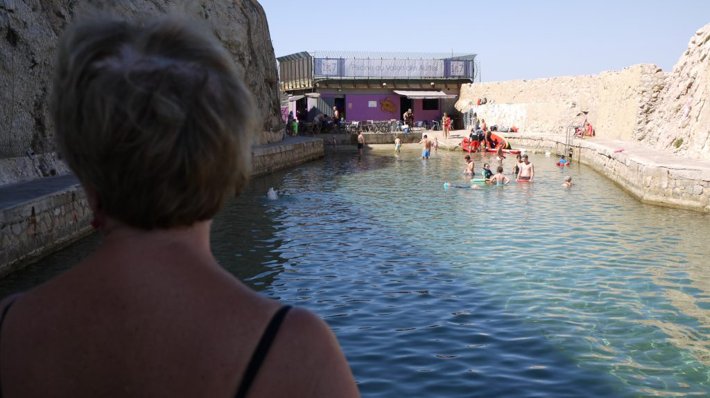 Andrée surveille ses petites-filles qui jouent dans la piscine naturelle.
