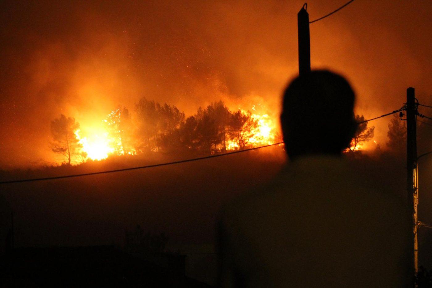 Un homme regarde le feu se déployer en face de son quartier aux Pennes-Mirabeau cette nuit.