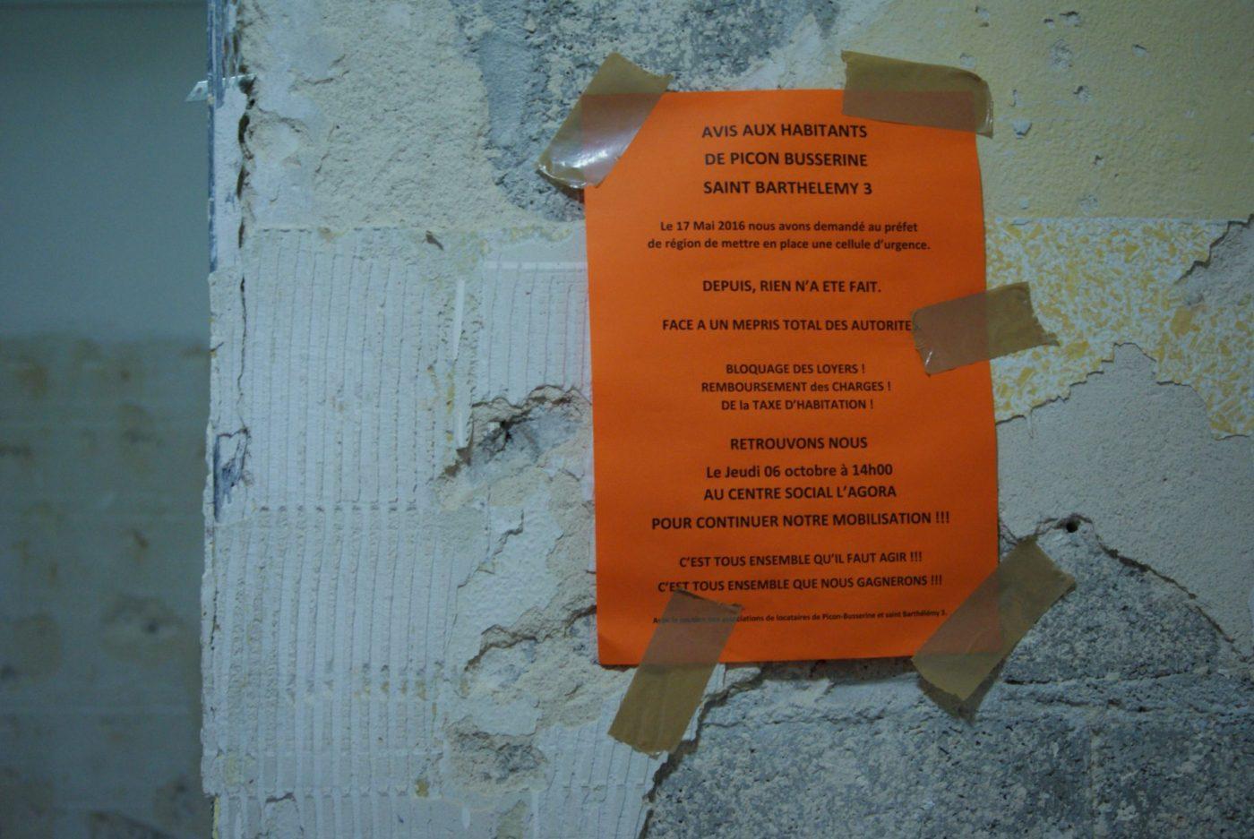 Une affiche annonçant aux habitants la venue de la délégation et appelant à la mobilisation, dans un hall d'entrée de la résidence Picon. (LC)